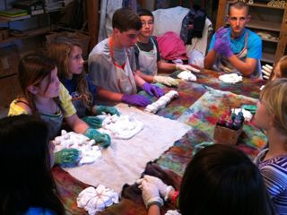 A group of children sitting around a table with t-shirts prepared for tie-dye