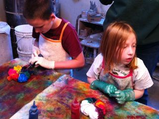 Two children applying colored dye to t-shirts